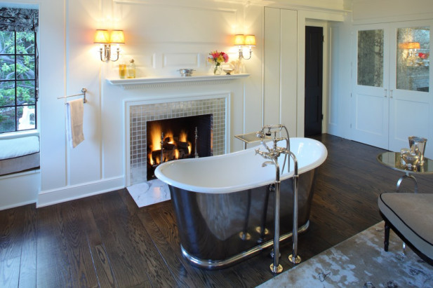 His and her bathrooms were divided off the master suite. The stunning tub is situated within the bathroom which includes a closet, dressing room, shower and vanity. Antique mirrors on the rich cream cabinet doors reflect the light of the chandelier over the island.