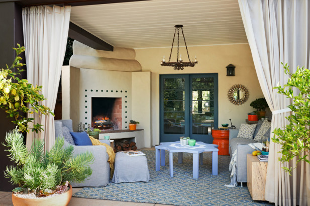 The drapery and potted plants frame an outdoor living room in blues and greys. A patterned fiber rug defines the area which features a welcoming fireplace, while the lounge chair and ottoman hug the corner near one of the posts.