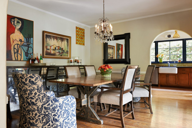 A warm and eclectic dining room features patterned side chairs that bring in an extra layer of texture. The walls exhibit vintage art, a map of London and a dark wood framed mirror.