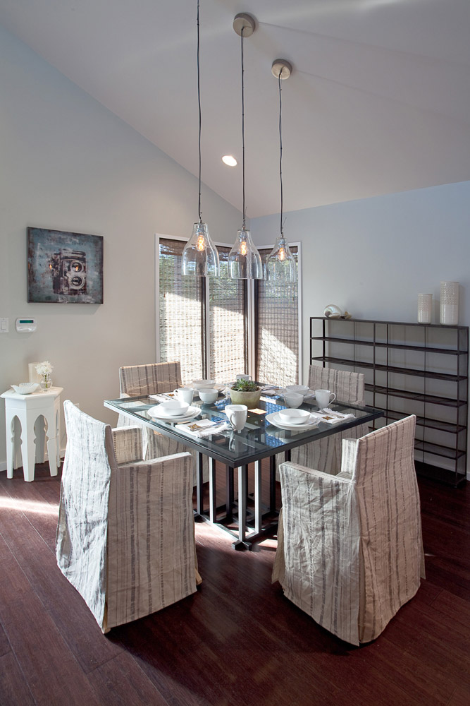 The dining room is bright and warm, with a museum-quality square table base with glass top which anchors the space. The chairs are slipcovered in our signature textile, while a wire console displays and stores surplus items.