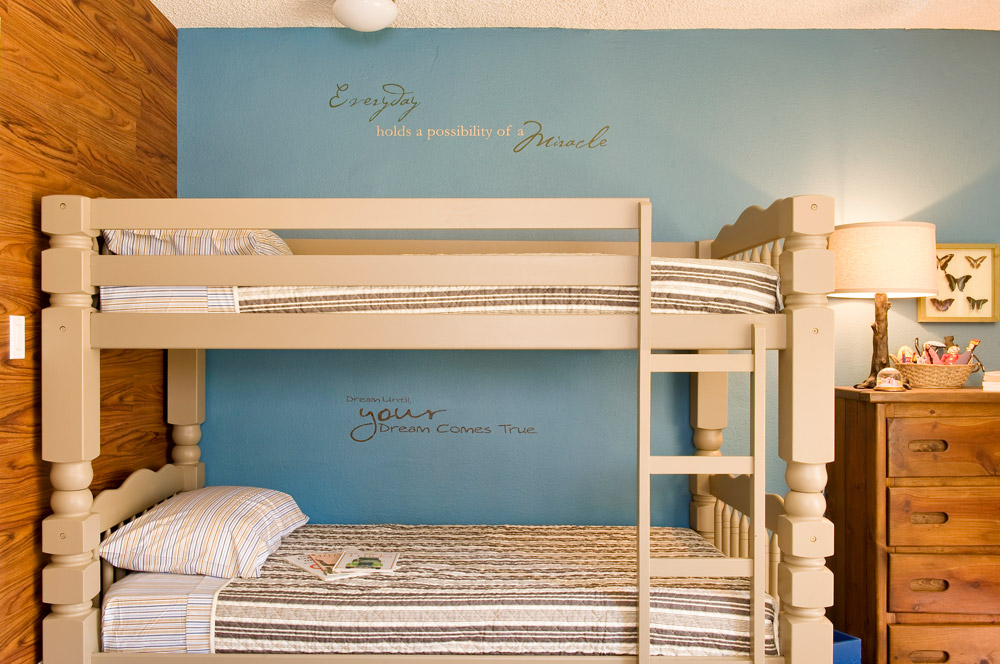 An emergency shelter for homeless families. Bunk beds in the children's area are custom painted in harmony with the slate blue wall and contrast with the wood wall and dresser.