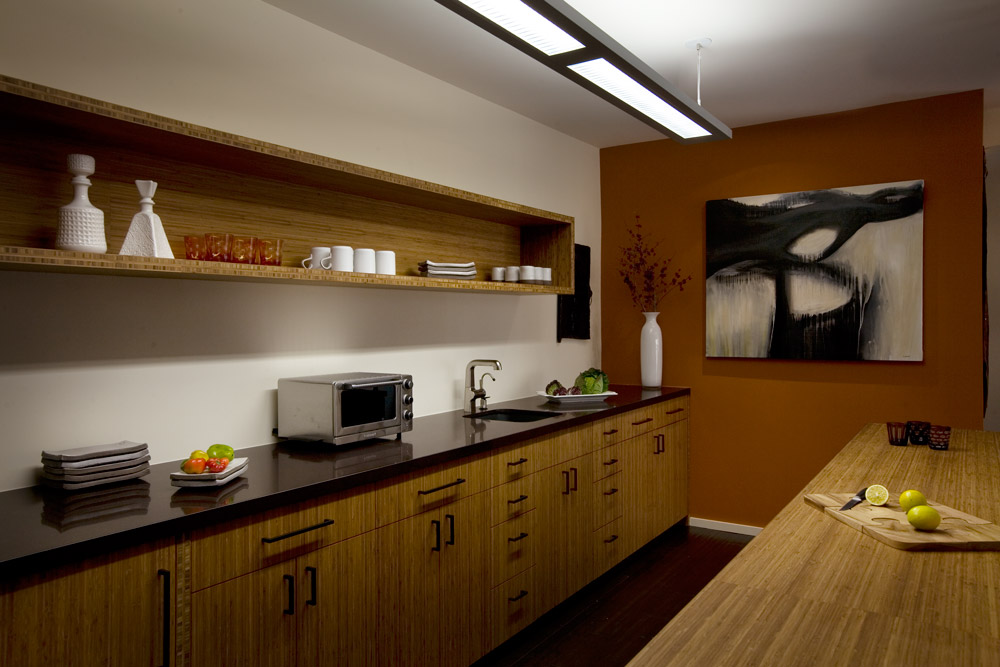 The office kitchenette takes an eco-zen approach to the water cooler — natural bamboo cabinetry is flanked by dark bamboo flooring and a burnt-orange accent wall.
