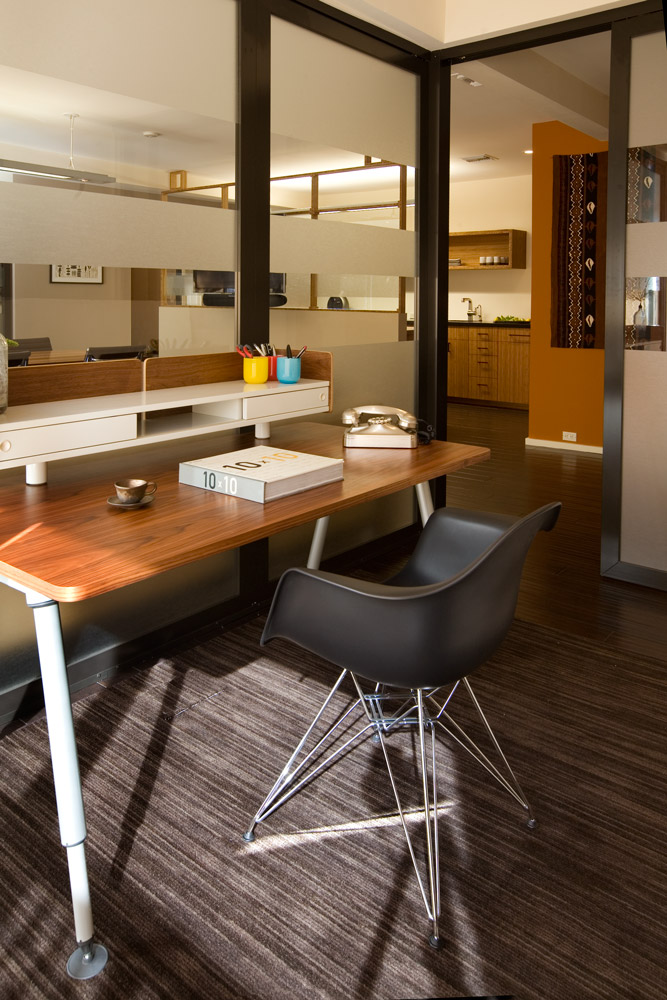 A small office is warmed with simple midcentury reproduction furniture.