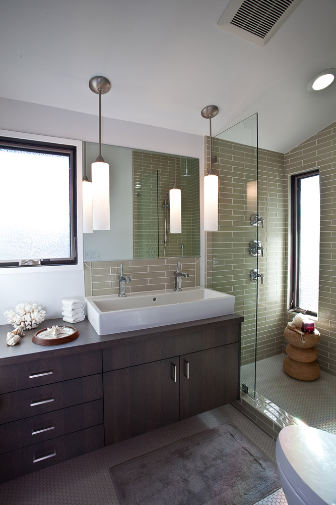 A serene master bathroom employs an oversized shower with glass accent tiles on the walls to add a subtle shimmer, while unglazed penny tiles on the floor, ground and lighten the space.