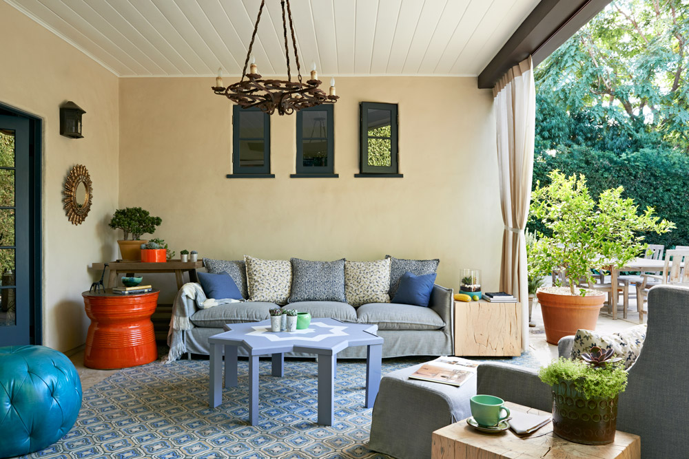 The outdoor sofa is soft and inviting. A mix of textures and patterns in the monochromatic blues adds visual interest, while a bright orange side table adds a fun burst of color. The Moroccan table in the center of the room was custom built for this space.
